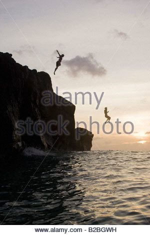Men jumping from cliffs into ocean - Stock Photo