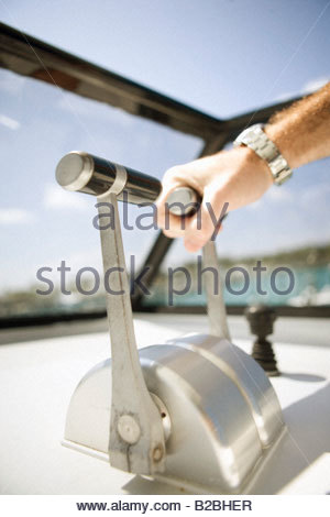Man's hand on boat throttle - Stock Photo