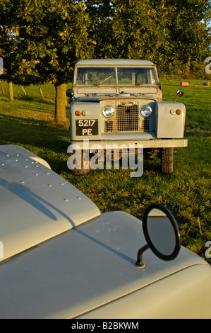 A matching couple of two historic 1963 Landrover Series 2a's on a farm in Dunsfold, UK 2004. - Stock Photo
