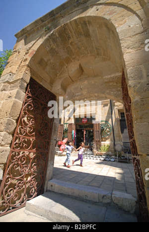 NORTH CYPRUS. Children running down a street in North Nicosia, seen through the gateway to the Selimiye Mosque. - Stock Photo