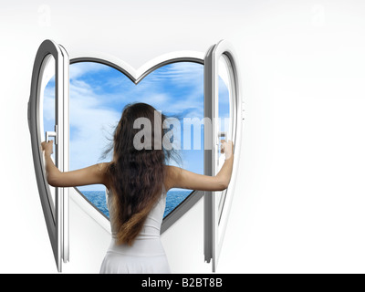 Beautiful woman wearing a white summer dress opening a heart-shaped window with a view of the sea, her long hair - Stock Photo