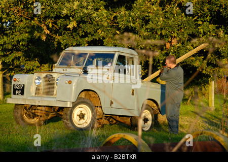 Workman in overall loading a timber beam into the back of a historic 1963 Landrover Series 2a truckcab in very original - Stock Photo