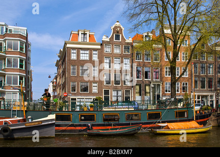 Houseboats in front of buildings along the canals in Amsterdam, Holland, the Netherlands, Europe - Stock Photo