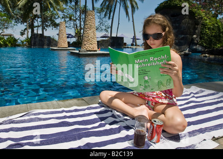 Ten year-old girl reading a book on german orthography during school holidays by the poolside, Lombok Island, Lesser - Stock Photo