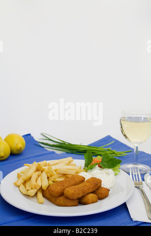 Fish fingers with chips, tartar sauce, white wine, chives and lemons - Stock Photo