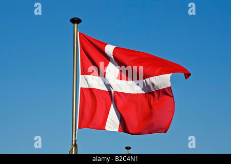 Danish Flag, Flag of Denmark, Dannebrog, fluttering in the wind on a flagpole - Stock Photo