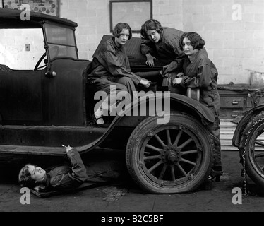 Female car mechanics fixing a car, historic picture from about 1920 - Stock Photo