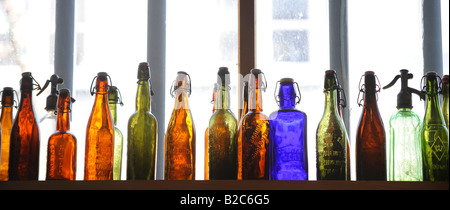 Colourful glass bottles in front of a window - Stock Photo