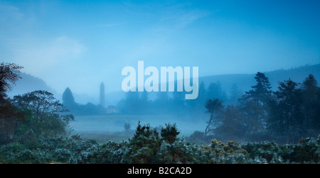 the round tower rising out of the mist at dawn at Glendalough, Wicklow Mountains, County Wicklow, Ireland - Stock Photo