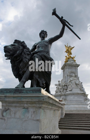 Bronze statue of a man and a lion, Queen Victoria Monument, in front of Buckingham Palace, London, England, Great - Stock Photo