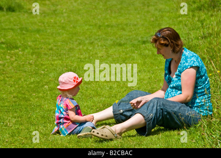 Horizontal portrait of 18-month old little girl sitting in the grass in the countryside with her mother on bright - Stock Photo