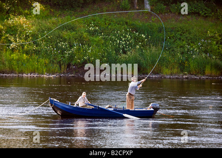 Rowing Boat fisherman, Angler Casting with Fly rod.Scottish Salmon Fishing using boats on the River Tay at Ballathie, - Stock Photo