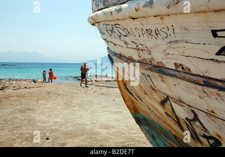 Old boat on a beach in Aegina - Stock Photo