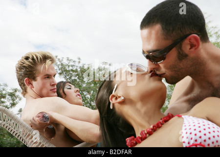 Young couple kissing at pool party. - Stock Photo