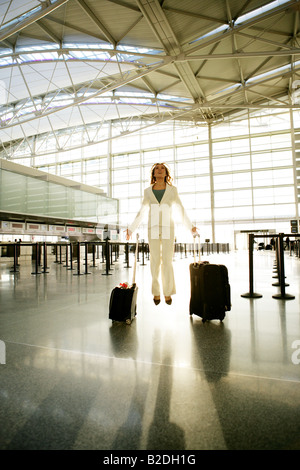 Young businesswoman levitating in airport. - Stock Photo