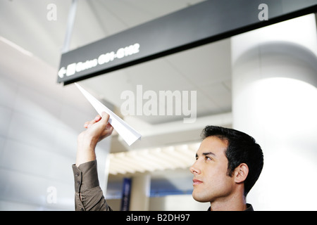Young businessman throwing paper airplane in airport. - Stock Photo