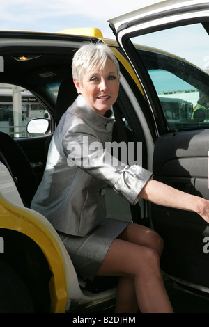 Mature woman getting in taxi at airport. - Stock Photo