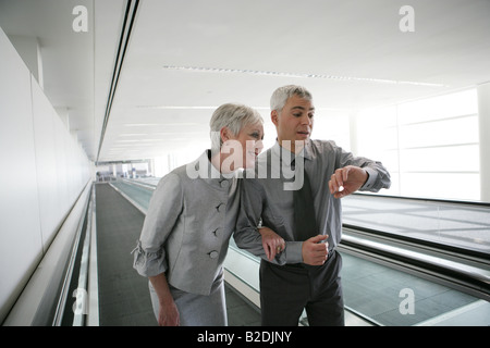 Mature couple on moving walkway at airport.