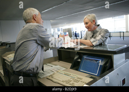 Airport attendant showing passenger brochure at check in counter. - Stock Photo