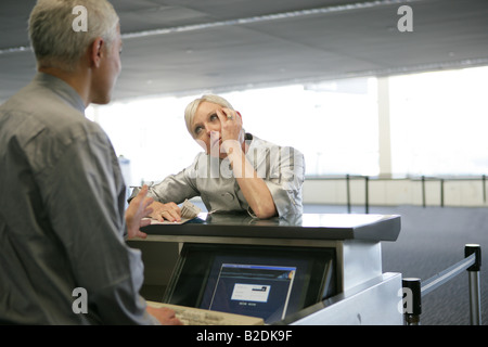 Stressed woman checking in at airport. - Stock Photo