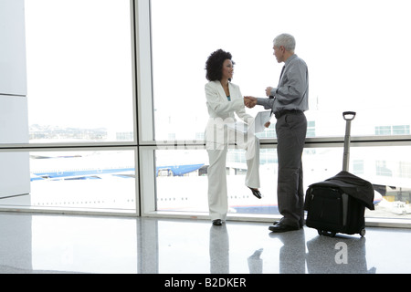 Businesspeople shaking hands in airport. - Stock Photo