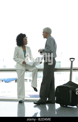 Businesspeople talking in airport. - Stock Photo