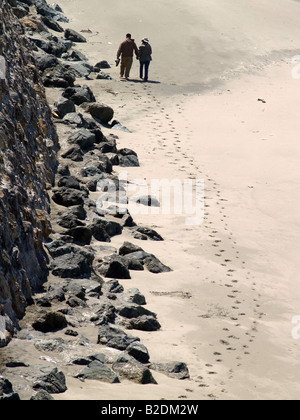 A couple walking hand in hand along a rocky beach - Stock Photo