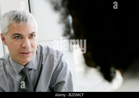 Mature businessman talking with colleage in airport. - Stock Photo