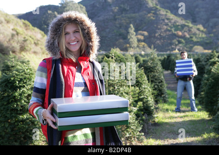 Young woman holding gift boxes outdoors with man behind. - Stock Photo