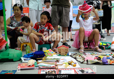 Teenages sell uesd goods at flea market on Sunday in a community in Beijing, China. 26-Jul-2008 - Stock Photo