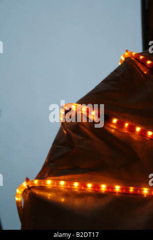bright christmas lights on property in city at night - Stock Photo