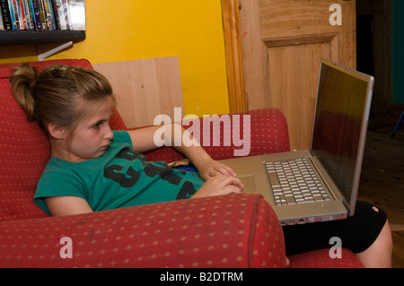 10 year old girl using a wireless connected Apple Mac Powerbook laptop computer at home, UK - Stock Photo
