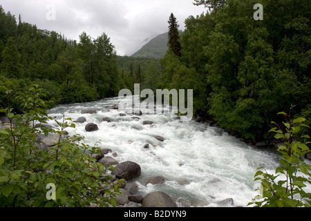 River running wild in a river rock bed in the Alaskan wilderness. - Stock Photo