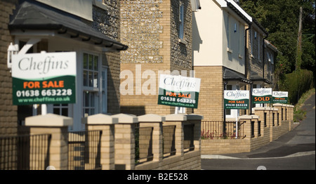A row of house for sale signs only one of which has been sold, Kentford Village, Suffolk - Stock Photo