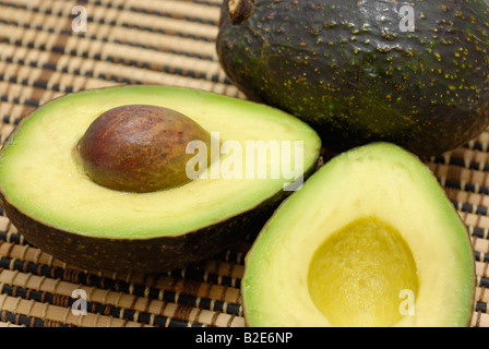 Avocados One Sliced in Half, Seed exposed - Stock Photo