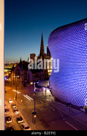 Lit up building with church in background at night Selfridges Building St Martins Church Birmingham England - Stock Photo
