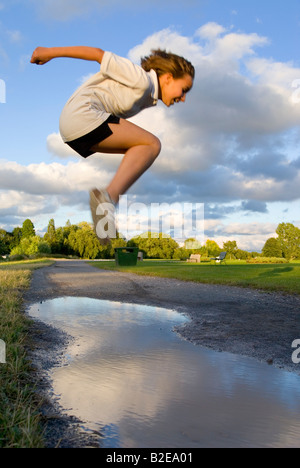 Side profile of girl jumping in mid air - Stock Photo
