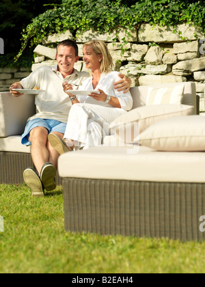 Couple eating food and smiling on couch - Stock Photo