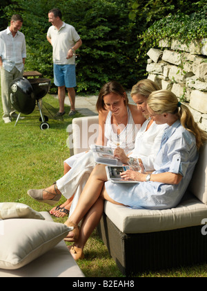Three women looking at photo albums on couch - Stock Photo