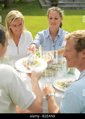 Group of people eating in garden - Stock Photo