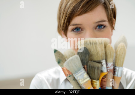 Portrait of a young woman holding paintbrushes in front of her face - Stock Photo