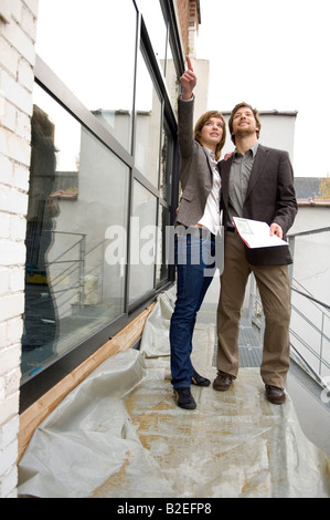 Young woman pointing forward and a mid adult man standing beside her - Stock Photo