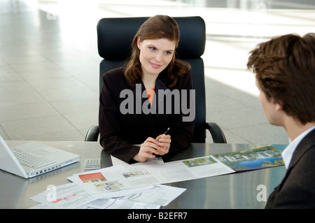Real estate agent explaining to a young man - Stock Photo