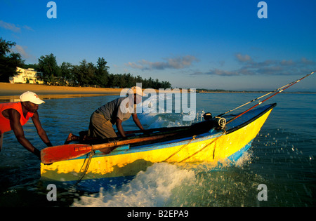 Two local fisherman launching their fishing boat out to sea - Stock Photo