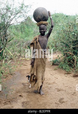 A Mursi girl, accompanied by her dog, carries a large clay pot to collect water from the Omo River. - Stock Photo