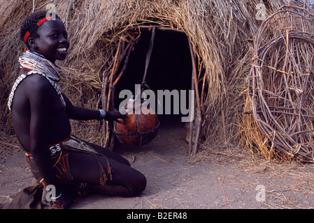 A Nyangatom girl churns butter in a gourd suspended in the entrance to her hut. - Stock Photo