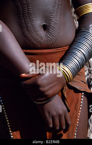 A Nyangatom woman with ornamental scarring on her stomach.  The scarrs are made with a razor and then infected with - Stock Photo