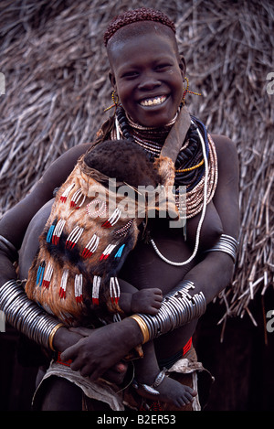 A young Nyangatom woman carries her baby on her hip in an elaborately braided papoose. - Stock Photo