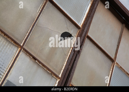 Rustic old windows and frames on an abandoned factory building with one broken glass pane. - Stock Photo