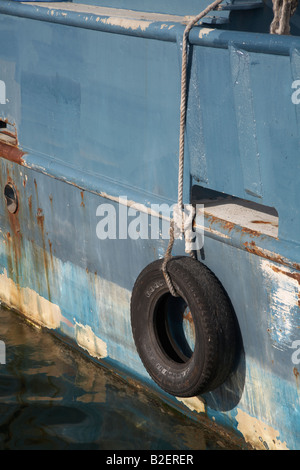 old tire on a rope hanging over the side of a boat - Stock Photo